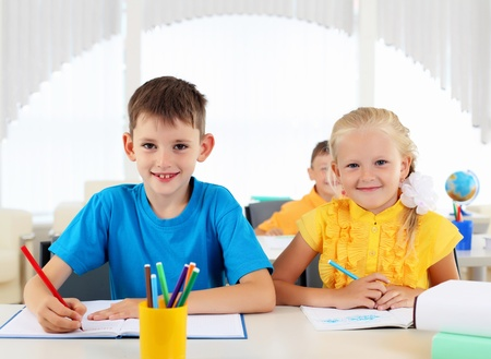 Boy and girl sitting together at a desk at school  photo