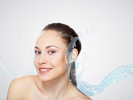 Portrait of beautiful young woman with water splashes photo