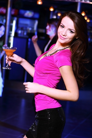 Young woman having fun and dancing at night club disco photo