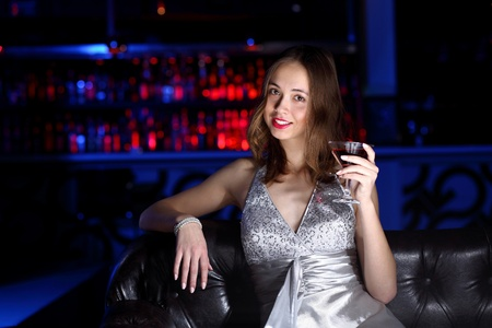 Young woman in evening dress in night club with a drink photo
