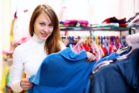 Retrato de la mujer joven en el interior de una tienda de compra de ropa