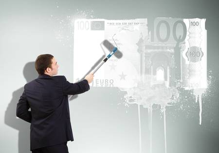 Young man with paint brush and banknote painted on the wall photo