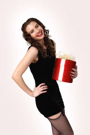Young pretty woman in black dress with a gift box photo