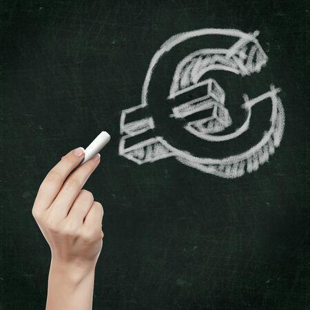 School blackboard and hand with chalk writing euro symbol on it Stock Photo - 12923728