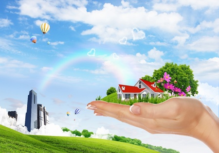 Human hand holding houses surrounded by nature against blue sky and rainbow photo