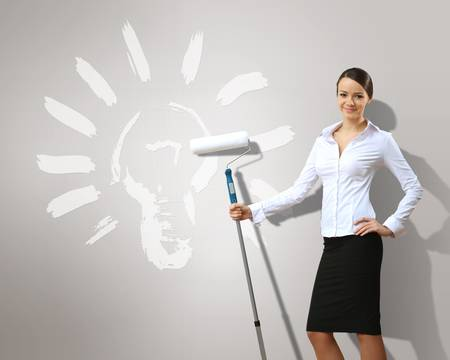 Businesswoman with paint brush and green energy symbols photo