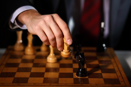 Image of a businessman in dark suit playing chess photo