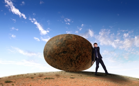work task: Image of businessman rolling a giant stone Stock Photo