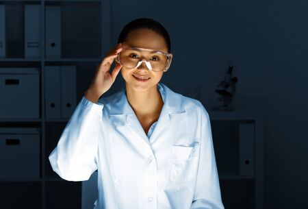 Young chemist in white uniform working in laboratory Stock Photo - 12995177