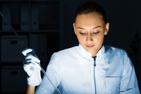 Young chemist in white uniform working in laboratory Stock Photo - 12995875