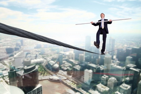 precipitate: Business man balancing on the rope high in the sky Stock Photo