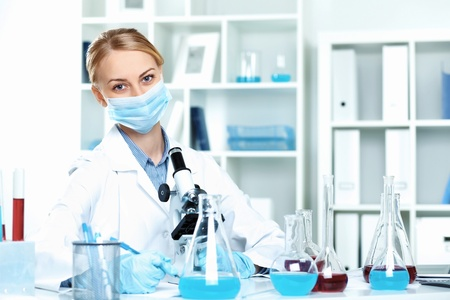 Young scientist in white uniform working in laboratory photo