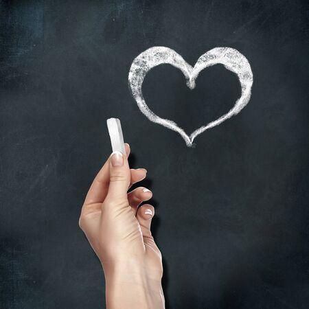 School blackboard and human hand with chalk drawing heart symbol Stock Photo - 13052747