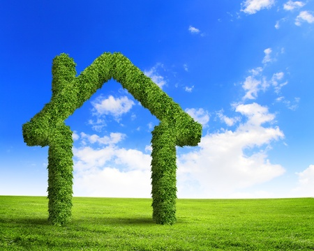 Green grass  house symbol against blue sky photo