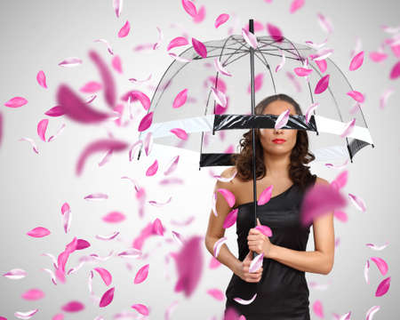 Pretty woman under umbrella with red petals around Stock Photo - 13146221