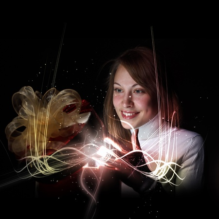 Young woman opening a gift box with shining and glittering lights around her Stock Photo - 13149090