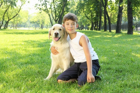 Teenager boy in the park with a golden retriever dog Stock Photo - 13191839