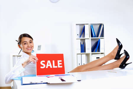 Young woman sitting in office in business wear with sale sign Stock Photo - 13087445