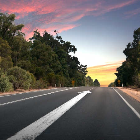challenging mission: Empty countryside road with white arrow sing on it Stock Photo