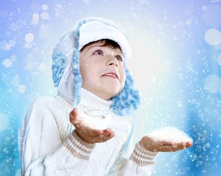 Portrait of little kid in winter wear against snow background photo