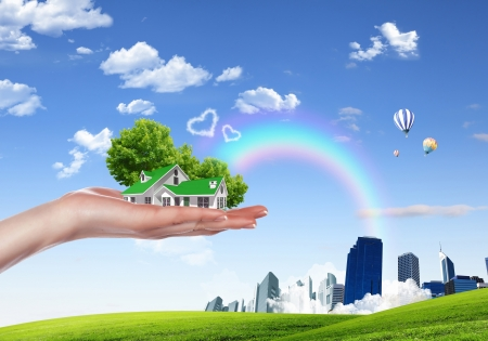 Human hand holding houses surrounded by nature against blue sky and rainbow Stock Photo