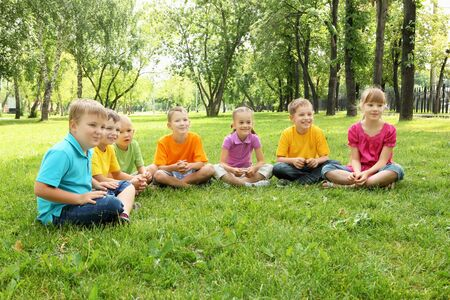 Group of children sitting together on teh grass in the park Stock Photo - 13171071