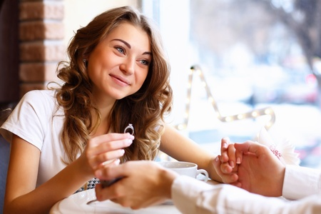 Young couple with a ring during an engagement in a restaurant photo