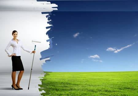 Businesswoman with a paint brush creating natural background photo