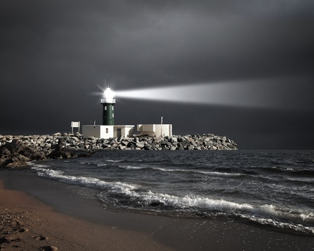 Image of a lighthouse with a strong beam of light photo