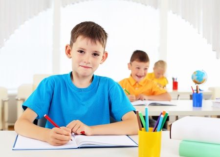 Portrait of a young boy sitting at his desk at school photo