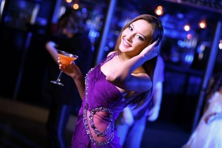 Young woman having fun and dancing at night club disco photo