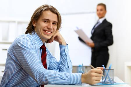 Young smiling happy businessman at work in office photo