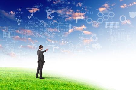 Jeune homme d'affaires en plein air avec des symboles d'affaires sur le fond de ciel
