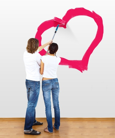 Young couple with paint brushes drawing heart on the wall photo