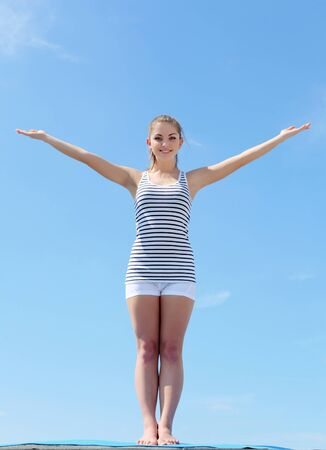 Portrait of a young woman doing exercises against blue sky photo