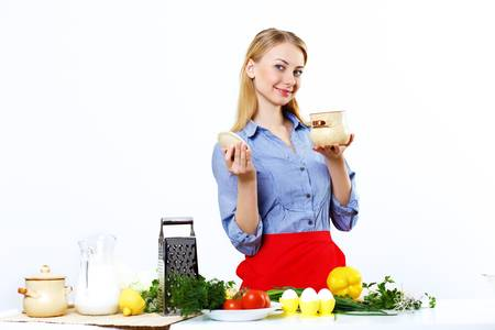 Young happy woman cooking fresh meal at home photo