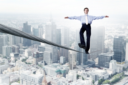 risky: Business man balancing on the rope high in the sky Stock Photo