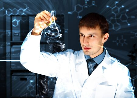 Young chemist in white uniform working in laboratory Stock Photo - 13201974