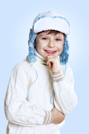 Portrait of little kid in winter wear against blue background photo