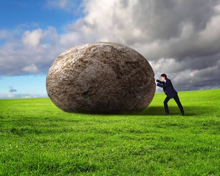sisyphus: Image of businessman rolling a giant stone Stock Photo