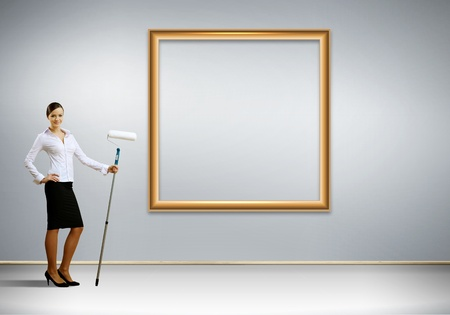 Young businesswoman with a paint brush against white wall photo