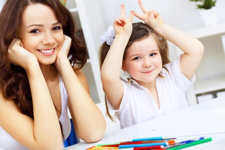 adults learning: Young mother with little daughter studying at home
