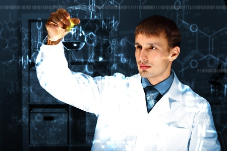 Young chemist in white uniform working in laboratory photo