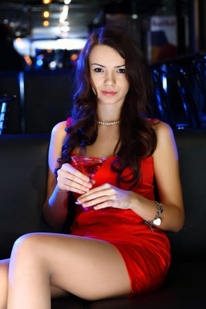 Portrait of young attractive woman in night club with a drink Stock Photo - 13224479