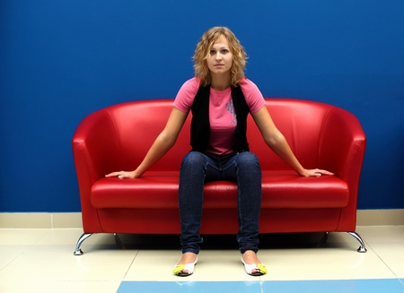 Portrait of young woman sitting on red sofa against blue wall photo