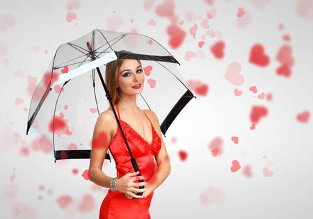 heart under: Pretty young woman with umbrella and with hearts on the background Stock Photo