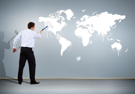 Businessman with paint brush and world map on the background photo