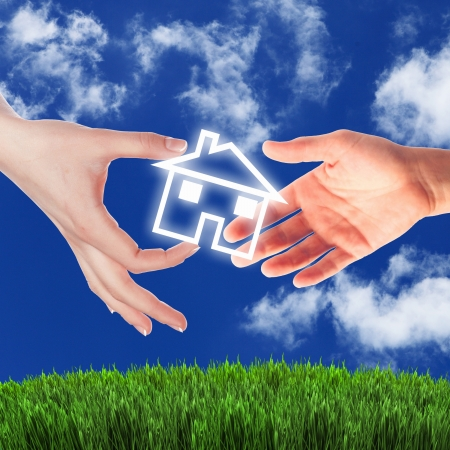 sell house: Human hand against blue sky background and house Stock Photo