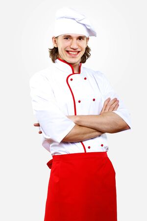 Portrait of a young cook in uniform preparing meal photo
