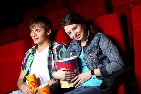 Young couple sitting in cinema and watching movie photo